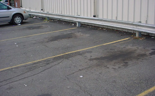 Photo of auto fluids leaked onto an impervious surface parking lot.