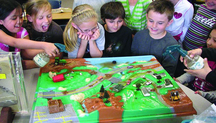 Children standing around an enviroscape
