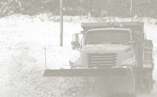 Photo of a snow plow doing winter road maintenance.